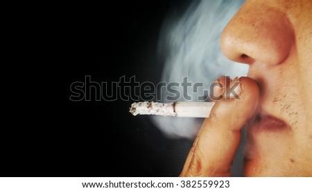 Man smoking cigarette on black background - stock photo