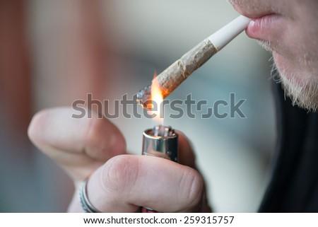 Man smoking marijuana cigarette soft drug in Amsterdam, Netherlands - stock photo