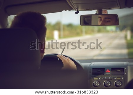 Man smoking marijuana while driving a car - stock photo