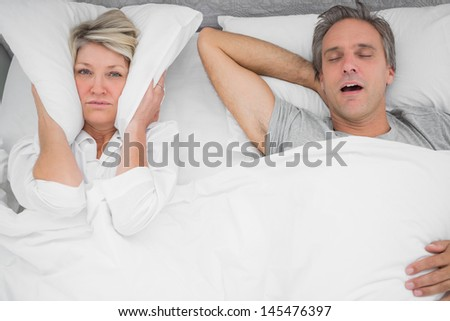 Man snoring loudly as partner blocks her ears at home in bedroom - stock photo