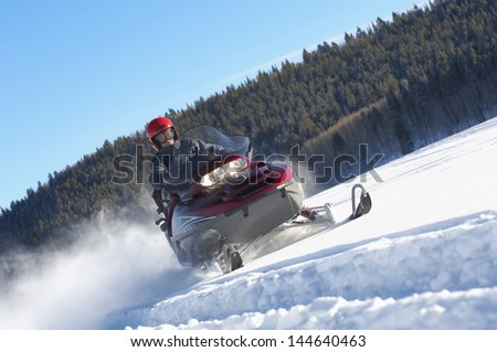 Man snowmobiling through snow in front of forest against blue sky - stock photo
