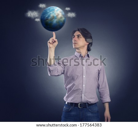 Man spinning on the finger of the planet earth. - stock photo