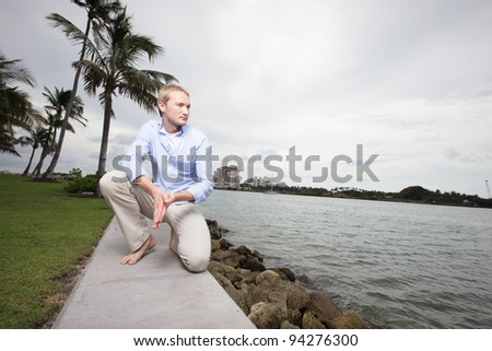 Man squatting by the bay - stock photo