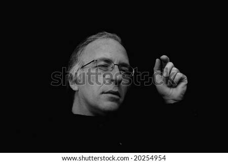 man squinting and gesturing with hand in this three quarter view portrait with dark background - stock photo
