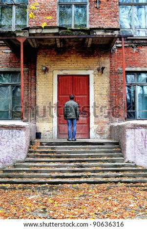 man stand in front of the old house with closed door - stock photo