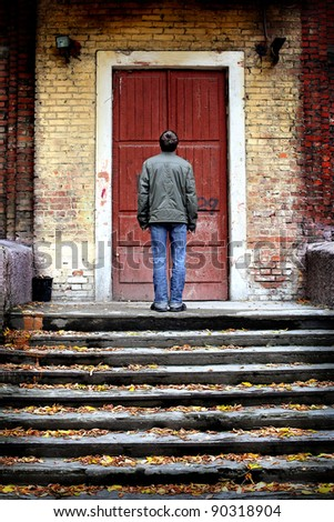 man stand on stairs of an old house with closed door - stock photo
