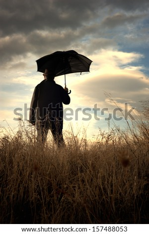 Man standing alone in the countryside watching at the cloudy horizon - stock photo