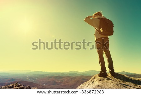 Man standing at the edge of a cliff overlooking the mountains below - stock photo