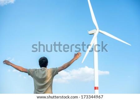 Man standing by wind turbine waving hands - stock photo