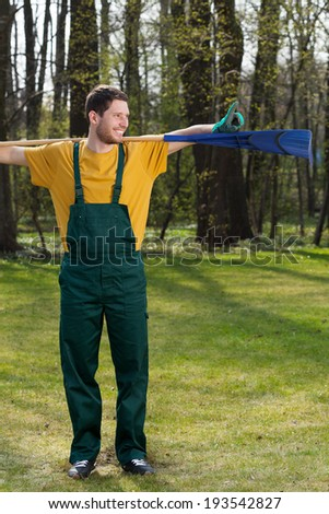 Man standing in a garden with a rake - stock photo