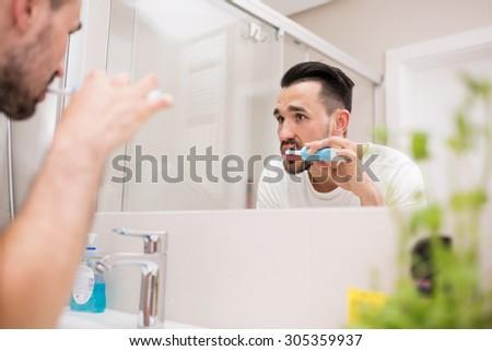 Man standing in bathroom and brushing teeth. - stock photo
