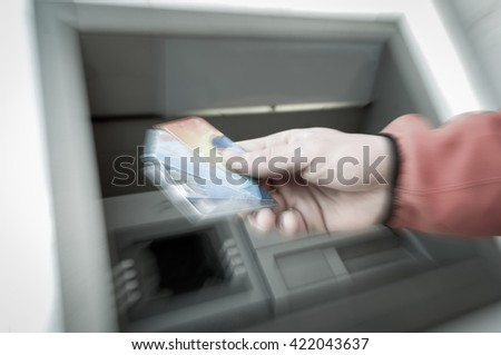 Man standing in front of an ATM machine, withdrawing money, holding a stash of credit and debit cards. 24/7 banking, automated banking, money fraud, debt and financial crisis concept. 