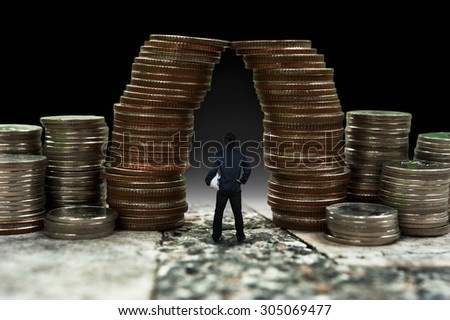 Man standing in front of giant coin pile, business concept - stock photo