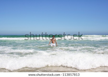 Man standing in indian ocean in south africa - stock photo