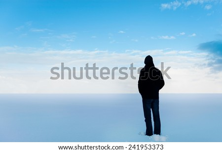Man standing in the snow, looking at the distance that he has to cross to come home. Seams pretty far! To go or not to go? - stock photo