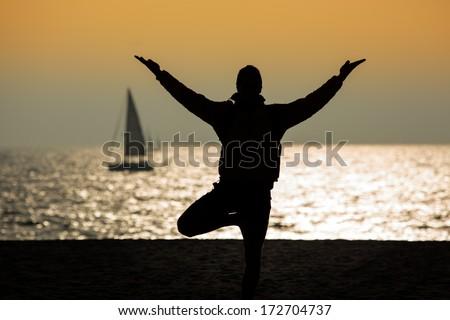 Man standing in tree yoga pose on ocean beach. - stock photo