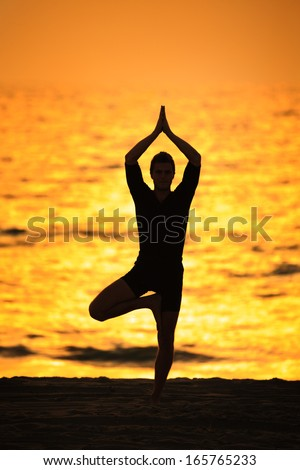Man standing in yoga tree pose on ocean beach at sunset - stock photo