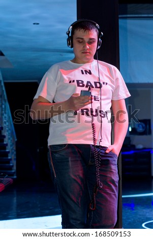 Man standing leaning against a pole relaxing listening to music on his headphones that he has downloaded onto his storage device - stock photo