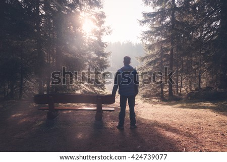 Man standing near bench at sunny morning forest - stock photo