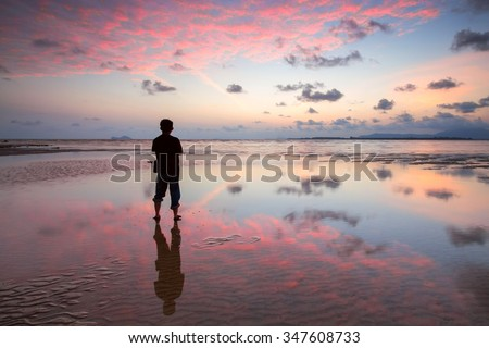 Man standing near the beach looking at beautiful sunset - stock photo