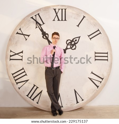 Man standing near the clock. Arrows show the big clock time. Male student or office worker. The clock at five minutes to two. Time to take a break for lunch and rest. - stock photo