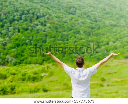 Man standing on a field with arms wide open,enjoying - stock photo