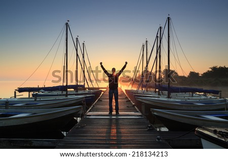 Man standing on a jetty in a marina during a foggy sunrise at a lake. - stock photo