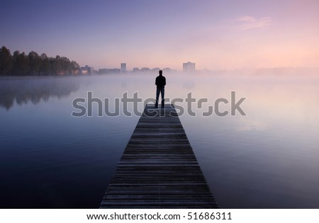 Man standing on a jetty looking at a city over foggy water at dawn. - stock photo