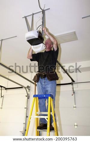 Man standing on a ladder fixing a mechanical garage door opener  - stock photo