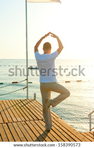 man standing on a pier on one leg and holds the balance - stock photo
