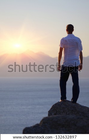Man standing on a rock by the sea and watch the sunset - stock photo