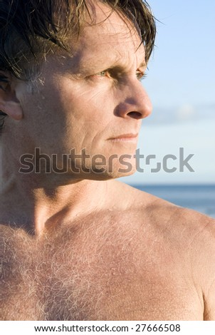Man standing on beach in profile. - stock photo