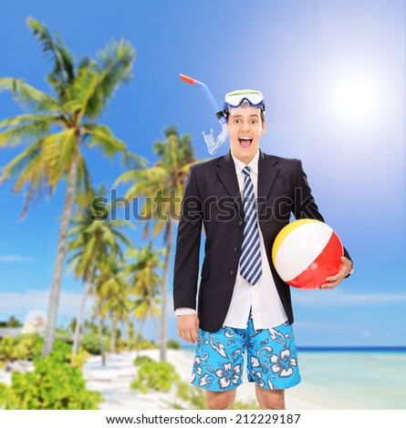 Man standing on beach with snorkel and beach ball shot with a tilt and shift lens - stock photo
