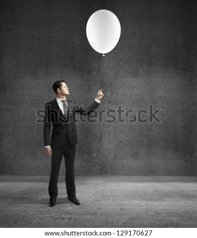 man standing on concrete room with balloon - stock photo