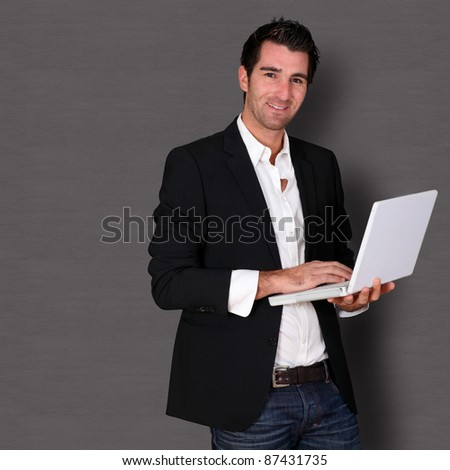 Man standing on dark background with laptop - stock photo