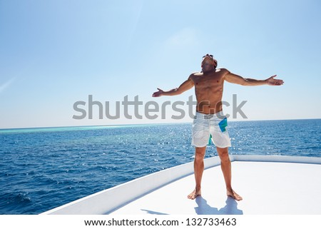 Man Standing On Deck Of Boat - stock photo