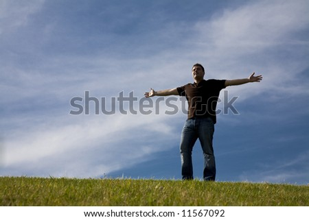 Man standing on Grass with his arms wide open - freedom concept - stock photo
