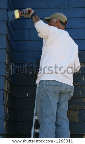 man standing on ladder painting outside of house - stock photo