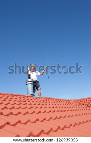 Man standing on rooftop of residential building to clean metal chimney of house with sweeper, with blue sky as background and copy space. - stock photo
