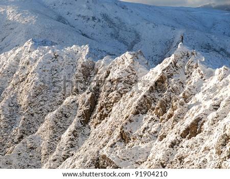 man standing on snowy mountain peak - stock photo