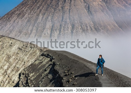 Man standing on the edge of Bromo volcano crater, Java, Indonesia - stock photo