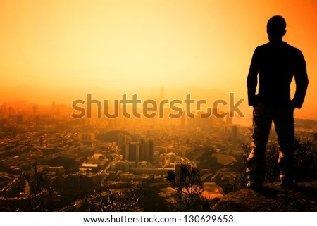 Man standing on the edge of Hong Kong's Lion Peak - stock photo