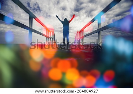 man standing on the edge of pier with hand open wide ,colorful bokeh ,freedom concept,inspiration and joy - stock photo