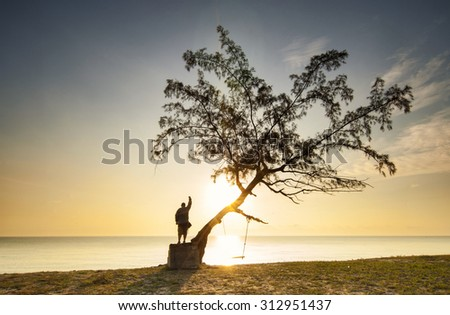 Man standing on the rock and the tree - stock photo