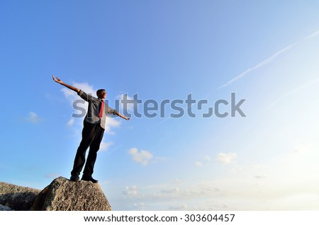 Man standing on the rock with his arms wide open - stock photo