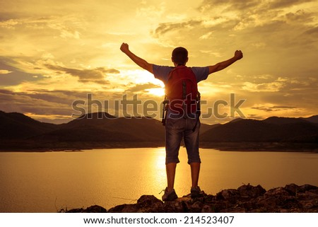 man standing on the shore of a mountain lake and raises his arms to the sky - stock photo