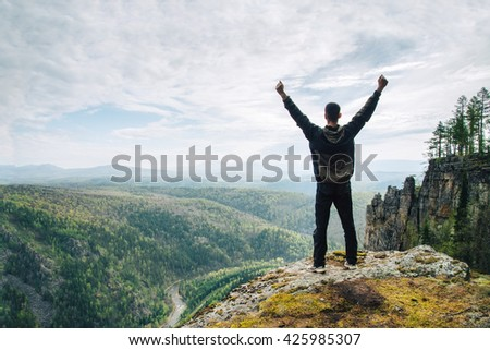 Man standing on the top of the mountain with raised up hands,  Russia, Ural, Bashkortostan, Aygir - stock photo