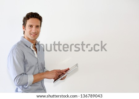 Man standing on white background with tablet - stock photo