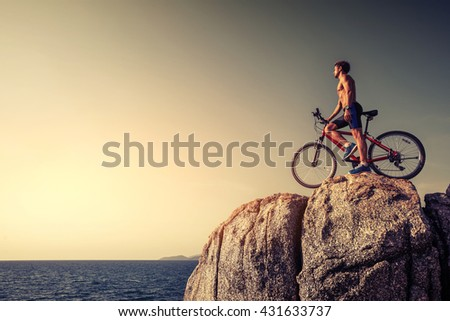 Man standing with a bicycle on the rock during sunset - stock photo