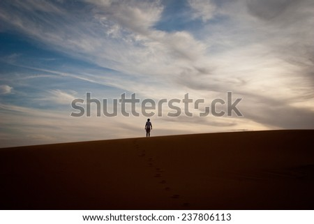 Man stands alone, on a dune in the Sahara Desert - stock photo